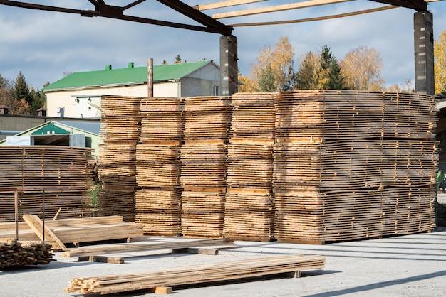 Stapel von holzbrettern im sägewerk, beplankung. lager für sägebretter auf einem sägewerk im freien. holzstapel aus holzrohlingen baumaterial. industrie.