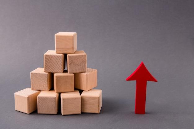 Stapel von holzwürfeln marktversorgung wächst mit rotem pfeil nach oben