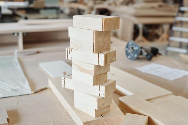 Stapel von holzziegelwerkstücken, die bei der herstellung von möbeln auf der werkbank eines modernen fabrikarbeiters verwendet werden können