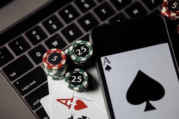 Stapel von hüften, smartphone und spielkarten auf der tastatur