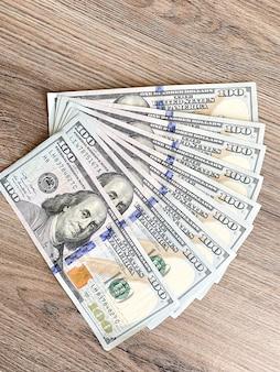 Stapel von hundert dollarscheinen auf hölzernem schreibtisch