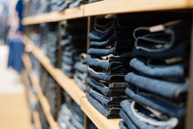 Stapel von jeans auf einem shopfenster im speicher