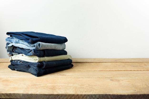 Stapel von jeans in einer wohnzimmereinstellung mit einer weißen wand