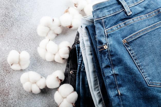 Stapel von jeanshosen und baumwollblumen auf hellem hintergrund