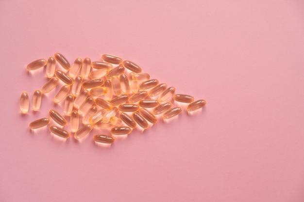 Stapel von kapseln omega 3 auf rosa hintergrund. nahaufnahme, draufsicht, hochauflösendes produkt.