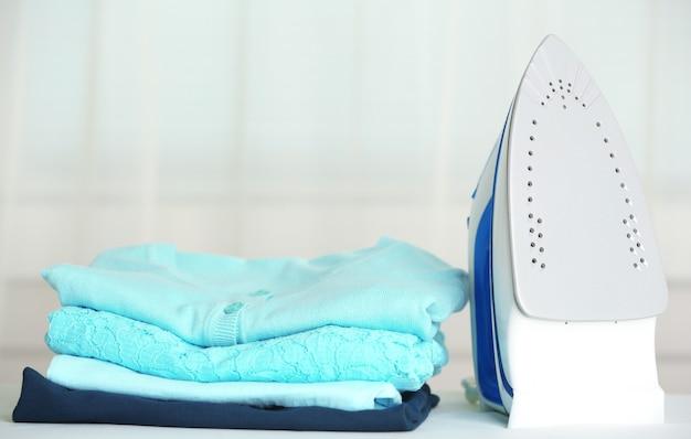 Stapel von kleidern und elektrischem eisen auf stoffhintergrund