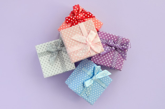 Stapel von kleine farbige geschenkboxen mit bändern liegt auf einem violetten hintergrund