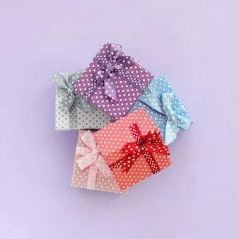 Stapel von kleine farbige geschenkboxen mit bändern liegt