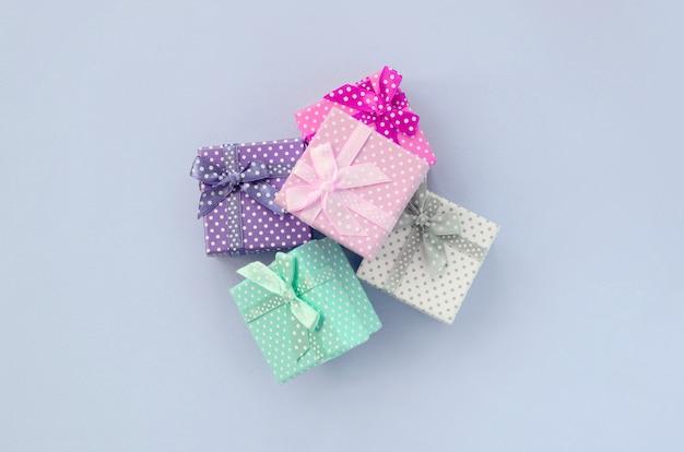 Stapel von kleinen farbigen geschenkboxen mit bändern liegt auf einem veilchen