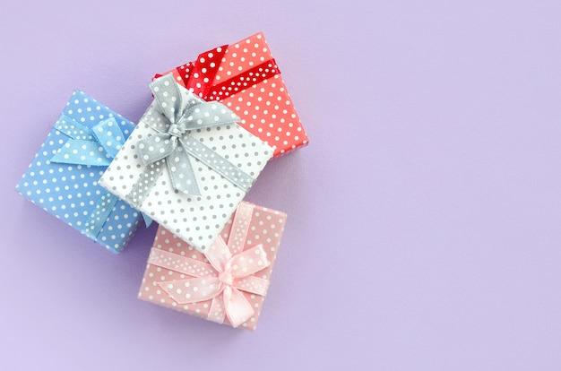 Stapel von kleinen farbigen geschenkboxen mit bändern liegt auf einem violetten hintergrund.