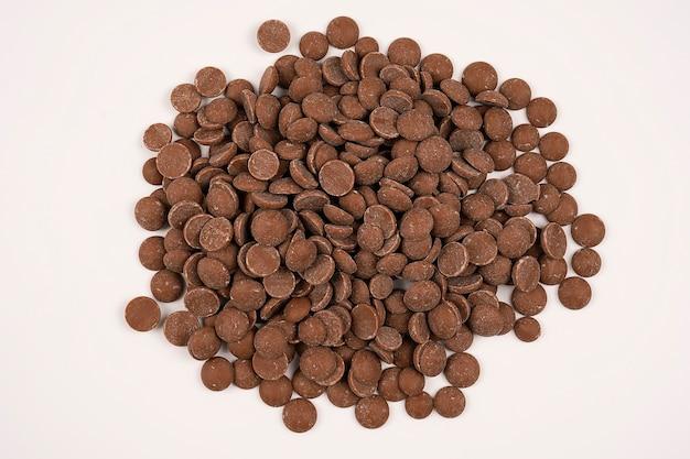 Stapel von köstlichen milchschokoladentropfen auf weißer nahaufnahme