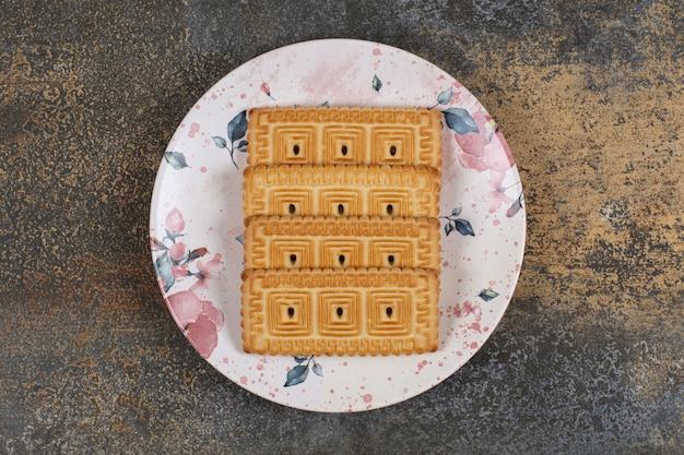 Stapel von leckeren keksen auf buntem teller.