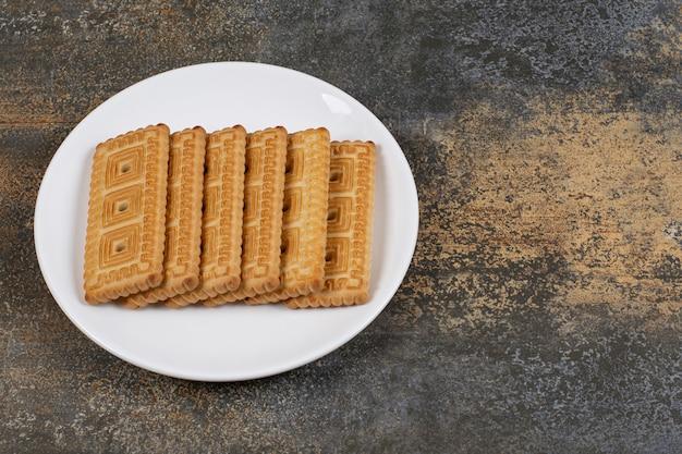 Stapel von leckeren keksen auf weißem teller.