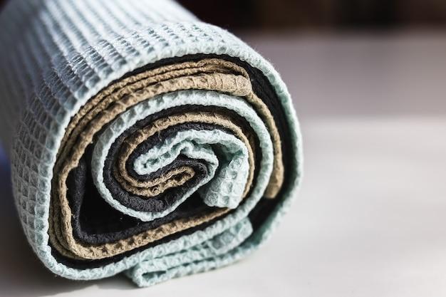 Stapel von matt gefärbten waffelleinen-baumwollserviettenhandtüchern auf weißem hintergrund. verschiedene farben. rolle küchentücher