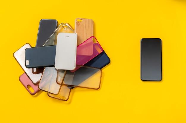 Stapel von mehrfarbigen plastikrückabdeckungen für handy auf gelb