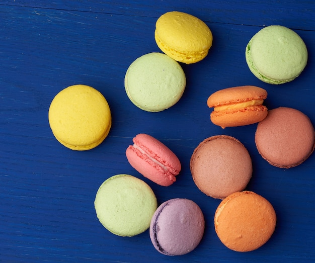 Stapel von mehrfarbigen runden gebackenen macarons-kuchen auf einem blauen hölzernen hintergrund, nahaufnahme