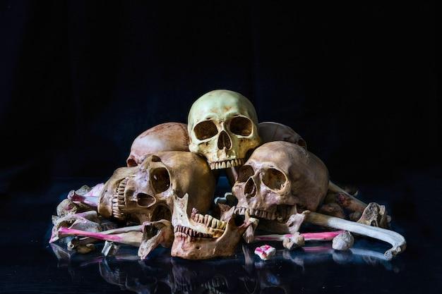 Stapel von menschlichen schädeln und von knochen auf dunklem hintergrund. halloween-konzept
