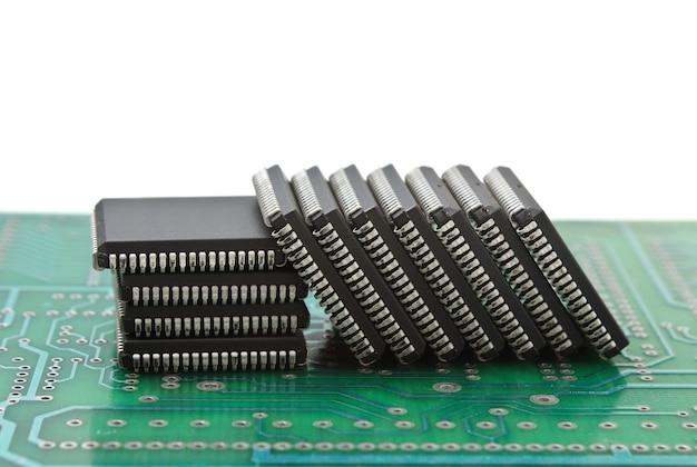 Stapel von mikrochips auf einer leiterplatte lokalisiert auf weißem hintergrund
