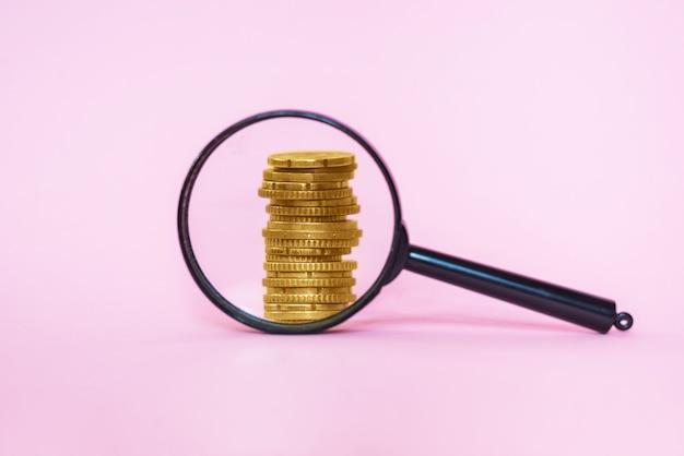 Stapel von münzen durch eine lupe auf rosa hintergrund. euro-münzen.