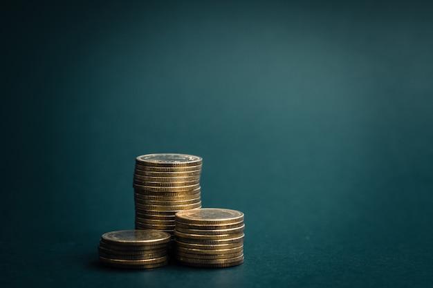 Stapel von münzen im dunklen raum angeordnet