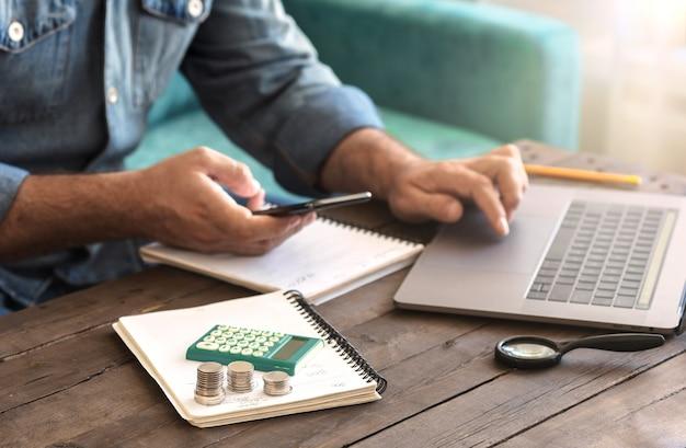 Stapel von münzen mit einem taschenrechner auf einem holztisch. mann, der hausfinanzierung prüft oder neues geschäftskonzept startet