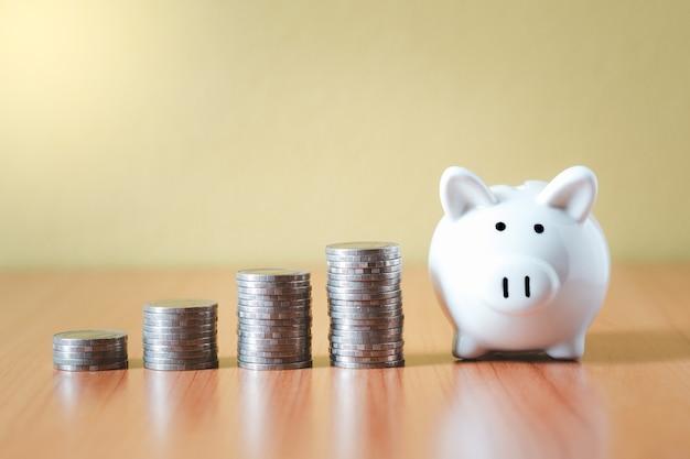 Stapel von münzen stapeln und weißes sparschwein für einsparungen mit geld und planungsschritt bis zum wachstum, geld sparen für pensionsfonds und das zukunftsplan-konzept.