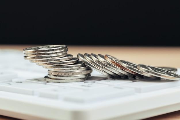 Stapel von münzen und taschenrechner