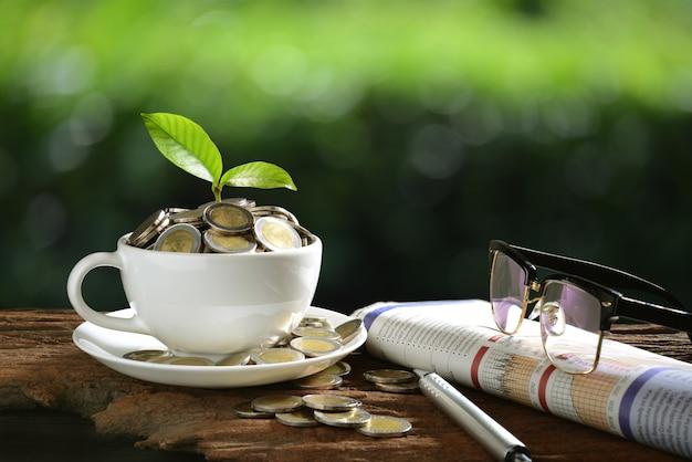 Stapel von münzen und von jungpflanze auf die oberseite in der kaffeetasse mit den zeitungen und gläsern, die geldtransferhintergrund zeigen