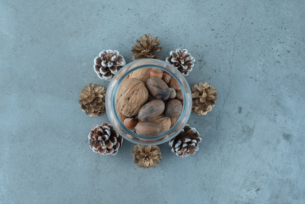 Stapel von nüssen in einem glas inmitten von tannenzapfen auf marmoroberfläche