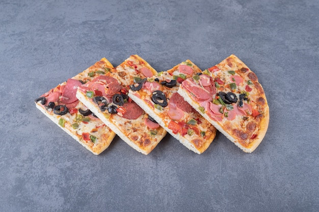 Stapel von peperoni-pizzastücken auf grauem hintergrund.