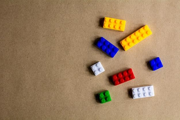 Stapel von plastikbausteinen auf hintergrund des braunen papiers