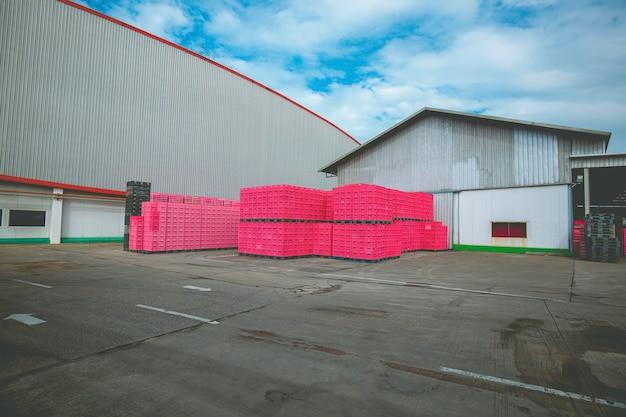 Stapel von plastikfarbenen rosa versandpaletten. industrielle kunststoffpalette im fabriklager gestapelt. fracht- und versandkonzept. palettenregal aus kunststoff für die exportindustrie.
