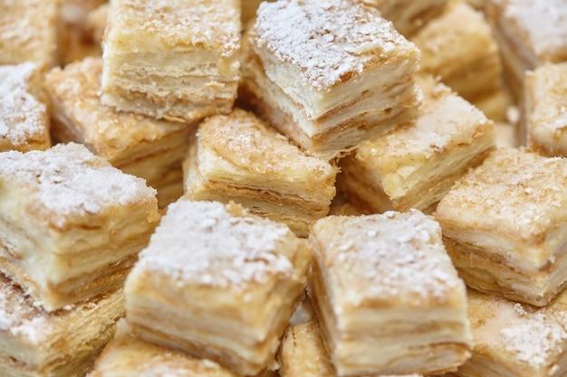 Stapel von quadratischen backscheiben schneidet desserts oder kuchen auf teller