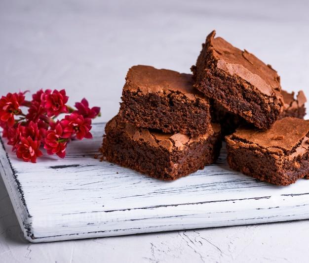 Stapel von quadratischen scheiben der gebackenen schokoladenkuchentorte