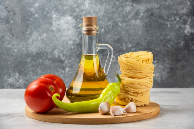 Stapel von rohen nudelnestern, flasche olivenöl und gemüse auf holzteller.