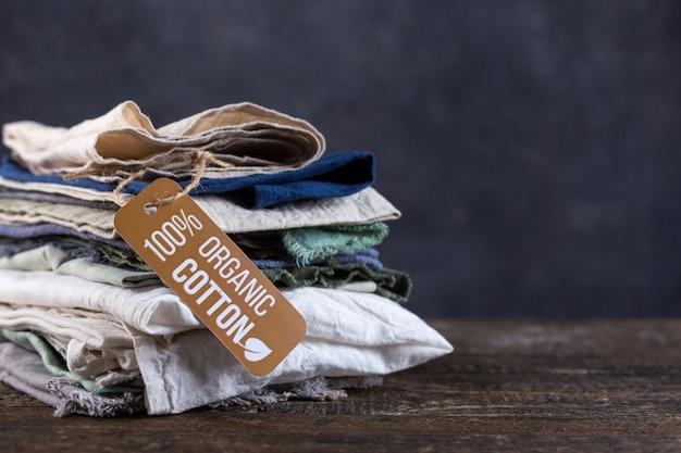 Stapel von sachen liegen auf einem holztisch. baumwolle, leinen in pastellfarben, hemden, stofffetzen, tücher.