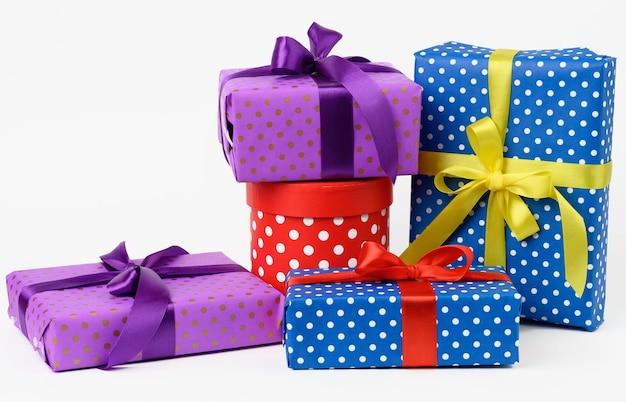 Stapel von schachteln in papier eingewickelt und mit einem seidenband auf weißem hintergrund gebunden, feier. geschenkboxen-set