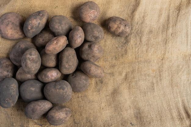Stapel von schmutzigen kartoffeln auf der linken seite einer jutematte