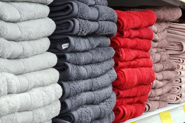 Stapel von schönen weißen, grauen, roten handtüchern in pastellfarben werden auf einer vitrine im laden verkauft. skandinavischer stil, lagom.