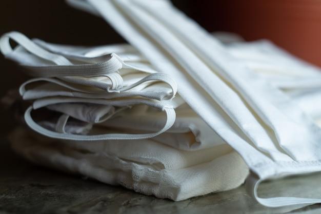 Stapel von schützenden antivirus-masken, die von ihren händen aus weißem stoff hergestellt wurden