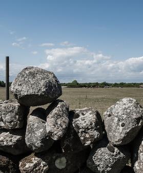 Stapel von steinen übereinander gestapelt als zaun in einem feld