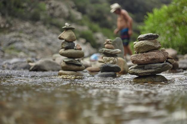 Stapel von steinen und kieselsteinen mitten im fließen eines baches