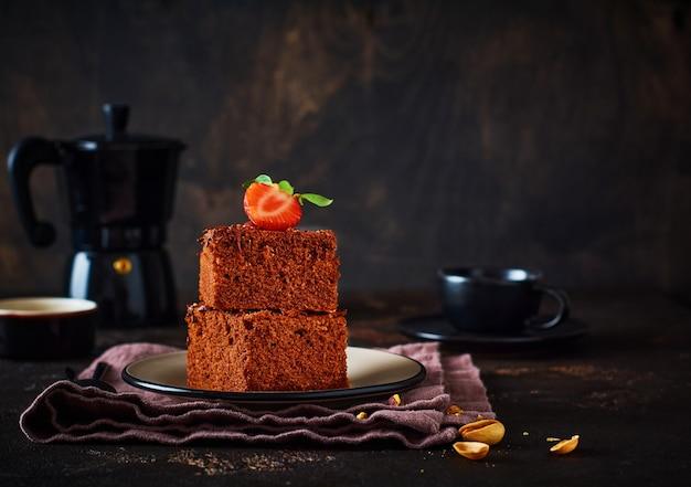 Stapel von stücken oder tafel schokoladenkuchen brownie mit erdbeeren und pistazien auf dem schwarzen hintergrund, selektives fokusbild.