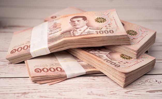 Stapel von thailändischen baht-banknoten auf hölzernem hintergrund.