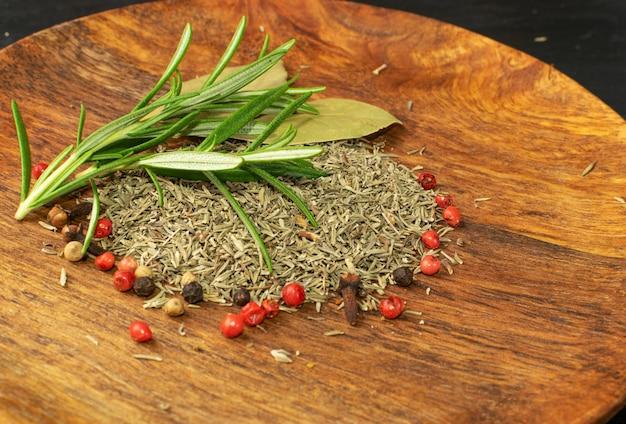 Stapel von trocken gehacktem thymian auf holztisch. getrocknete zerkleinerte oreganoblätter. gemahlenes thymusgewürz, frische grüne rosmarinkräuter und gewürze hautnah