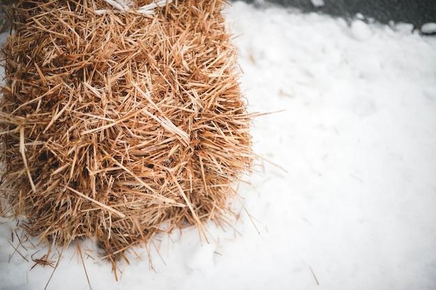 Stapel von trockenem gras auf einer mit schnee bedeckten oberfläche