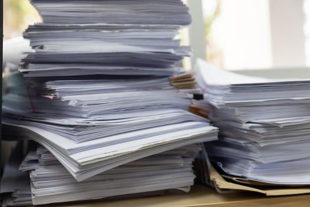 Stapel von unfertigen dokumenten auf schreibtisch