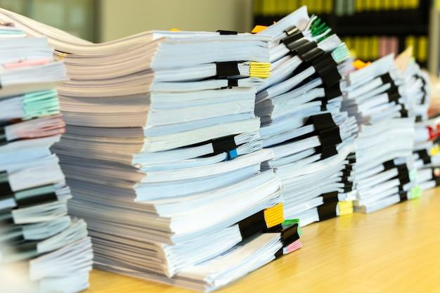 Stapel von unfertigen dokumenten auf schreibtisch.
