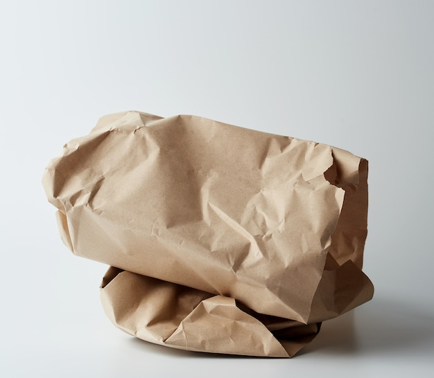Stapel von verdrehten braunen blättern papier auf einer weißen oberfläche
