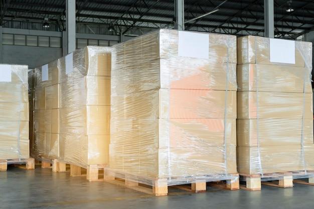Stapel von verpackungsboxen, die plastik auf palette im lager einwickeln